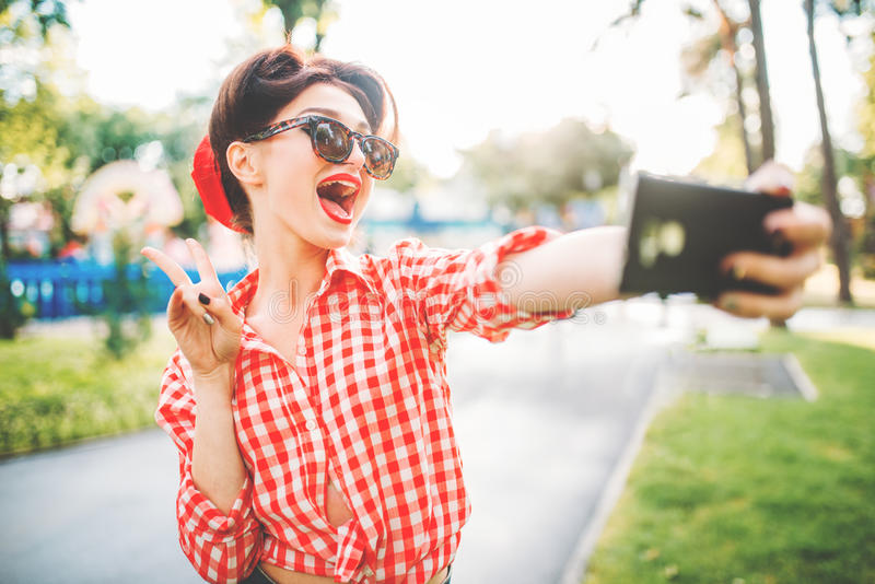 Pinup lady makes selfie on camera in park. Pinup lady makes selfie on phone camera in park, fifties american fashion. Attractive model in pin up style stock images
