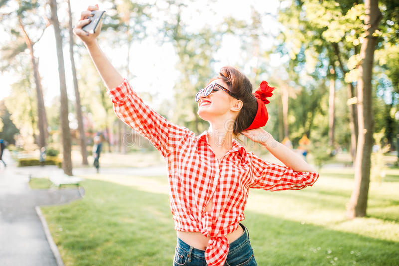 Pinup lady makes selfie on camera in park. Pinup lady makes selfie on phone camera in park, fifties american fashion. Attractive model in pin up style stock image