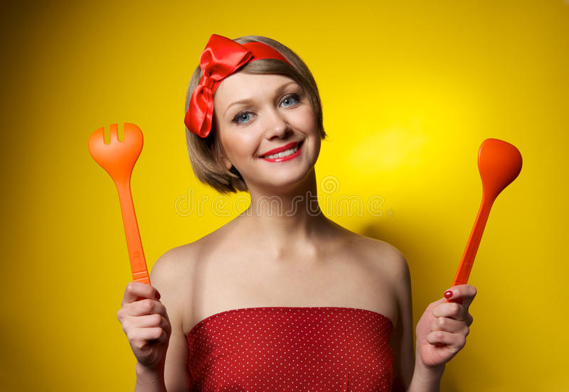 Pinup style housewife with kitchen utensils royalty free stock photos
