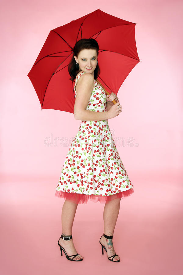 Pinup Woman in Cherry Dress. A pinup style photo of a woman in a cherry covered dress holding a red umbrella. The background is a pastel pink color stock images