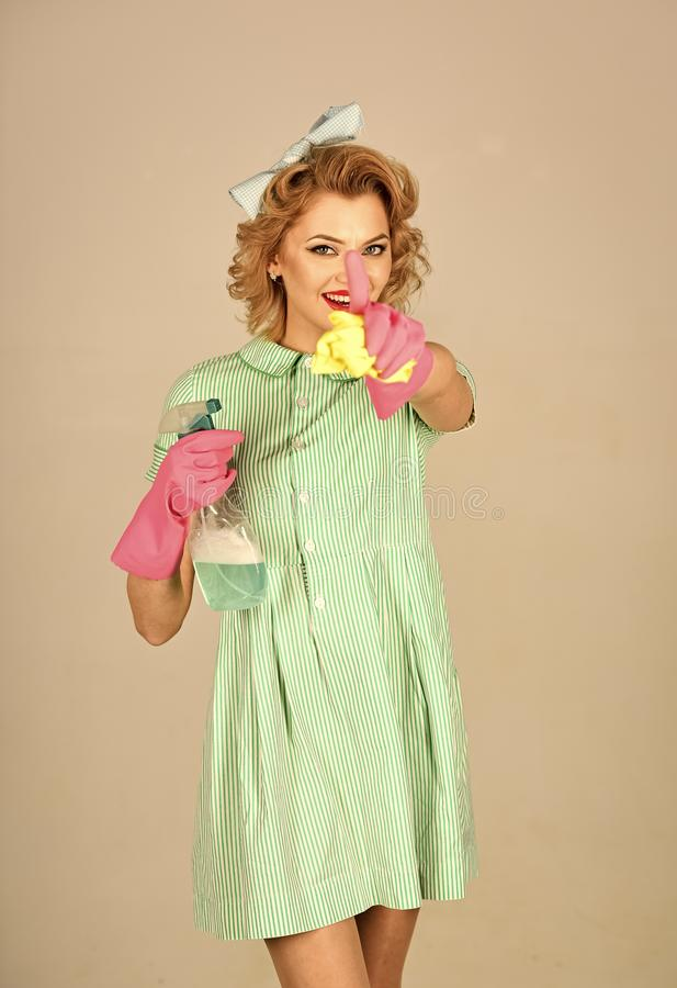 Pinup woman hold soup bottle, duster. Cleaning, retro style, purity. Retro woman cleaner on grey background. Cleanup, cleaning services, wife, gender stock photo
