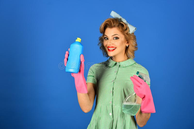 Pinup woman hold soup bottle. Retro woman cleaner on blue background. Cleanup, cleaning services, wife, gender. Housekeeper in uniform with clean spray stock photography