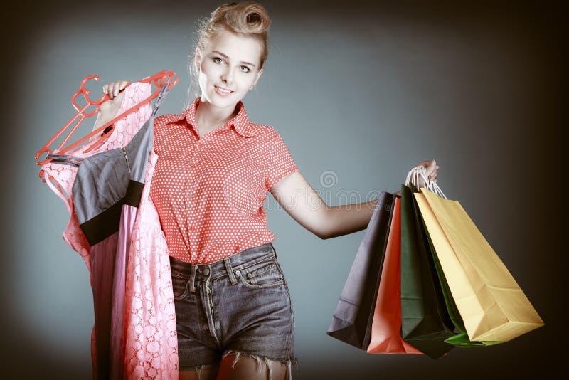 Pinupmädchen mit Einkaufstaschen Kleidung kaufend Verkauf lizenzfreie stockfotografie