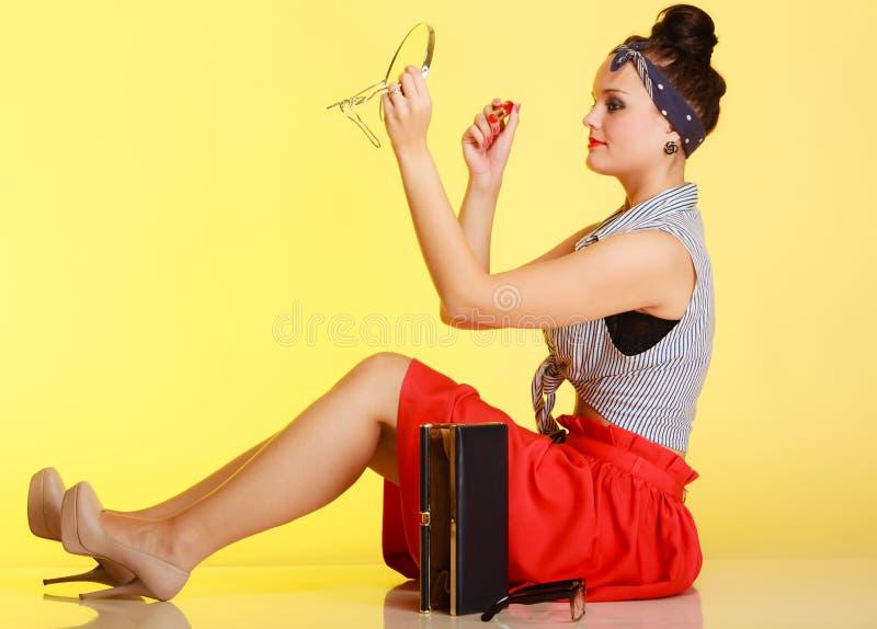 Pinupmädchenfrau, die Make-up auf Gelb anwendet. lizenzfreie stockfotos