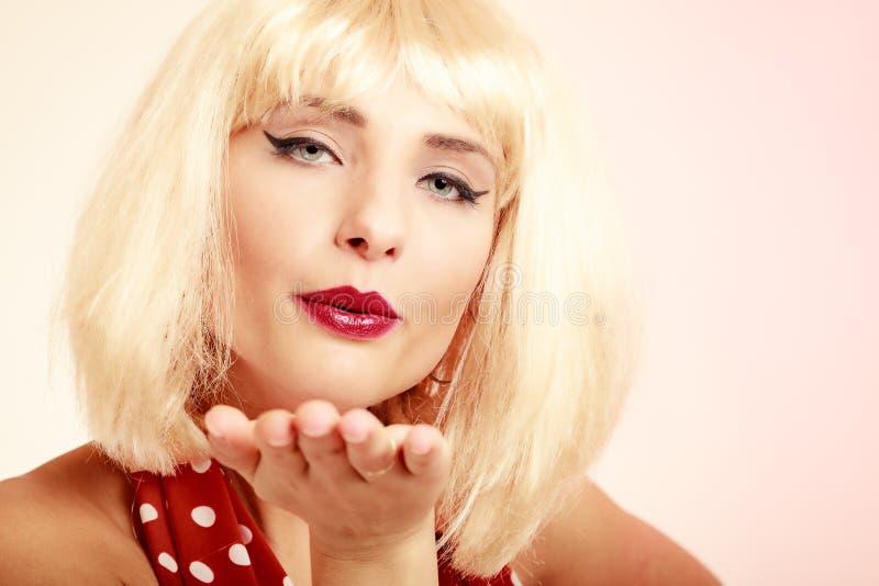 Pinupmeisje in blonde pruiken retro kleding die een kus blazen stock foto's