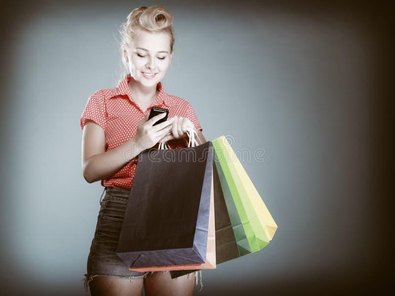 Pinupmeisje met het winkelen zakken die op telefoon texting stock foto