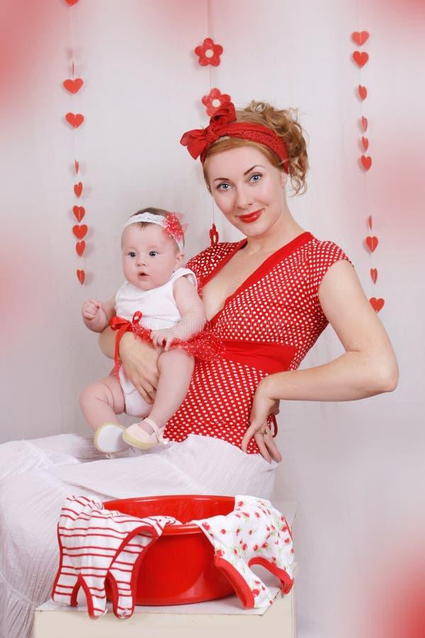 Pinupmoeder en babymeisje met wasserij stock foto's