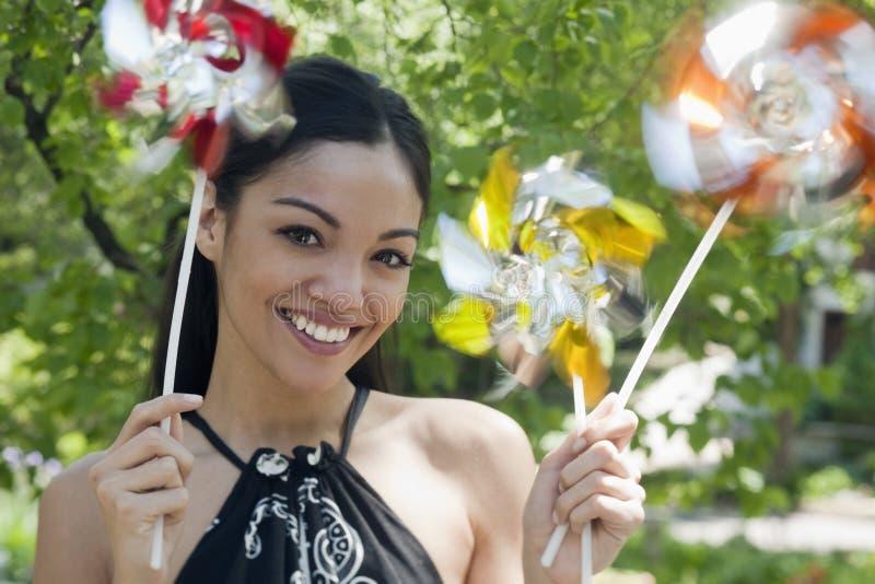 Pinwheels de fixation de jeune femme photo stock