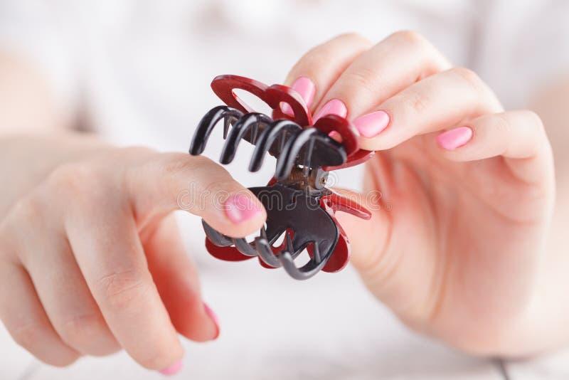 Pinza de pelo en mano femenina fotos de archivo libres de regalías