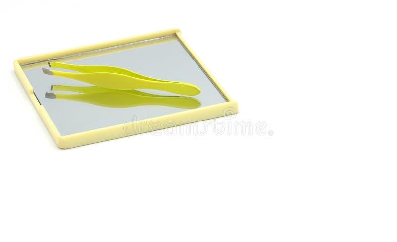 Pinzas con el espejo aislado en el fondo blanco foto de archivo
