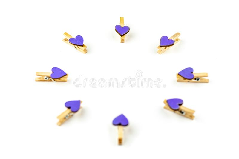 Pinzas con los corazones púrpuras aislados en el fondo blanco del fondo Concepto festivo en el estilo mínimo para el día de tarje imagen de archivo