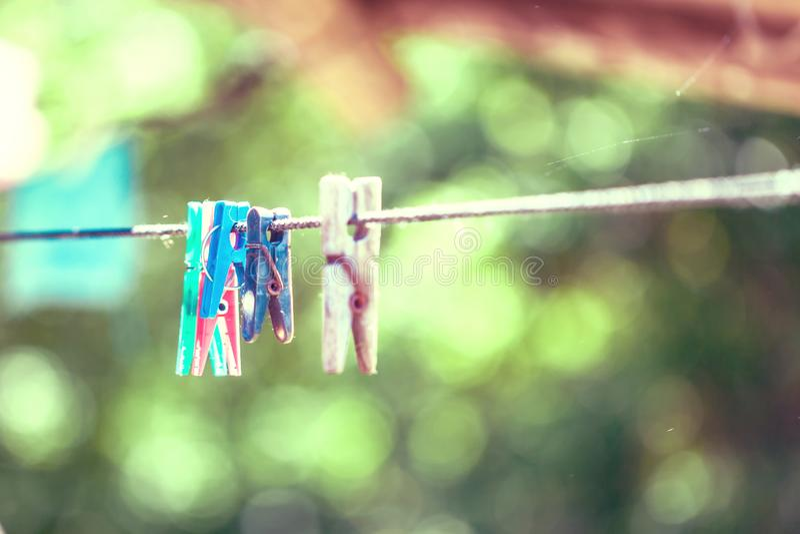 Pinzas de lino en una cuerda blanca, fondo del verdor del bokeh fotografía de archivo libre de regalías