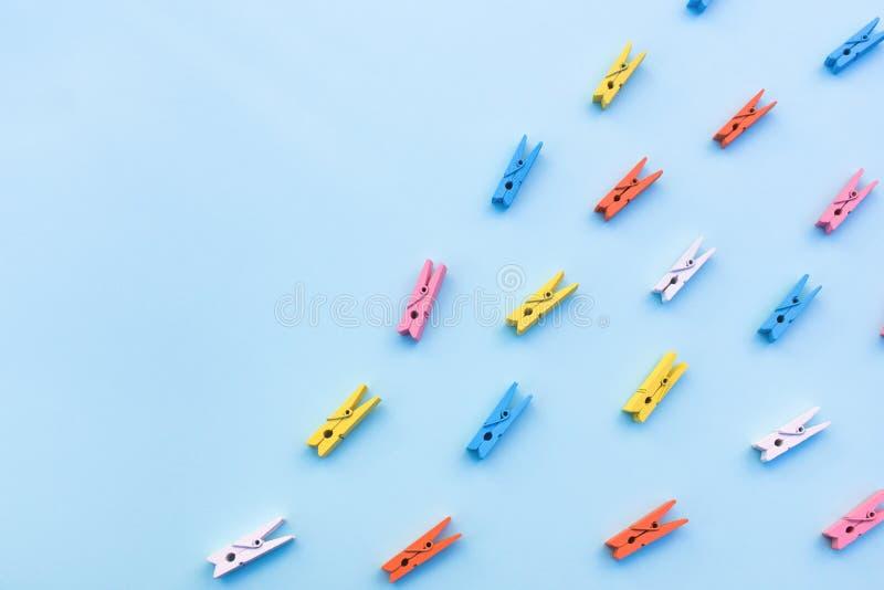 Pinzas multicoloras en un fondo azul imagenes de archivo