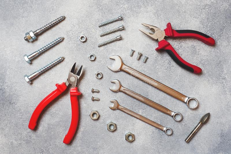 Pinze, cacciaviti e combinazione della chiave su fondo concreto grigio con lo spazio della copia Strumenti ergonomici professiona immagine stock libera da diritti