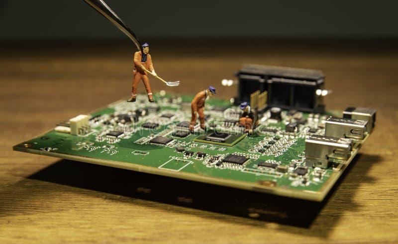 Pinzette mit einem kleinen Ingenieurmodell und zwei Ingenieuren vorbildlich auf Leiterplatte lizenzfreies stockbild