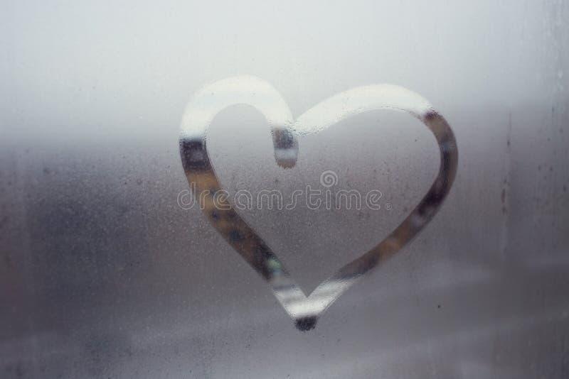 Pioggia di autunno, l'iscrizione sul vetro sudato - ami il cuore fotografia stock
