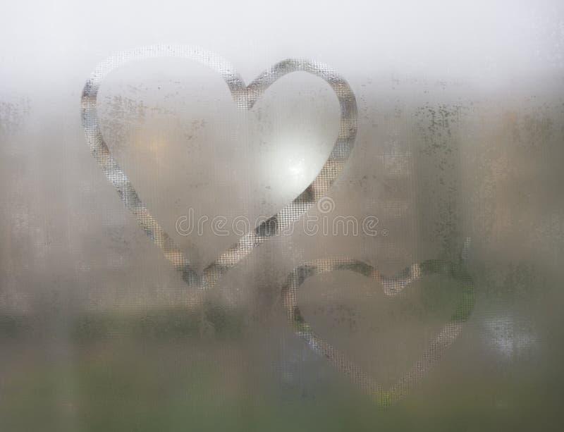 Pioggia di autunno, l'iscrizione sul vetro sudato - amore e cuore fotografia stock libera da diritti