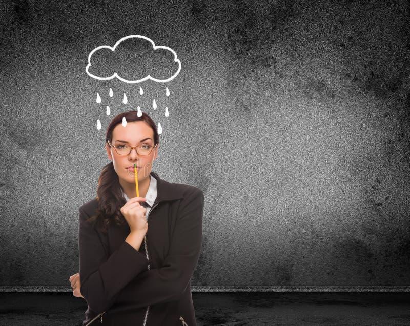 Pioggia e nuvola estratte sopra la testa di giovane donna adulta con la matita davanti alla parete con lo spazio della copia fotografia stock