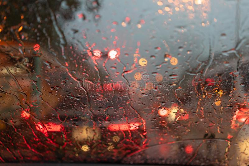 Pioggia vaga astratta mentre l'automobile è in mezzo alla strada alla luce della coda dell'automobile di notte che riflette con l fotografia stock libera da diritti