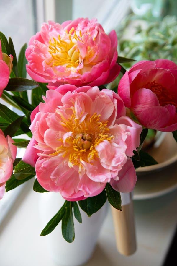 Pionbuketten av blommor på ett ben i inre av restaurangen för en beröm shoppar floristry eller att gifta sig salongen royaltyfri fotografi