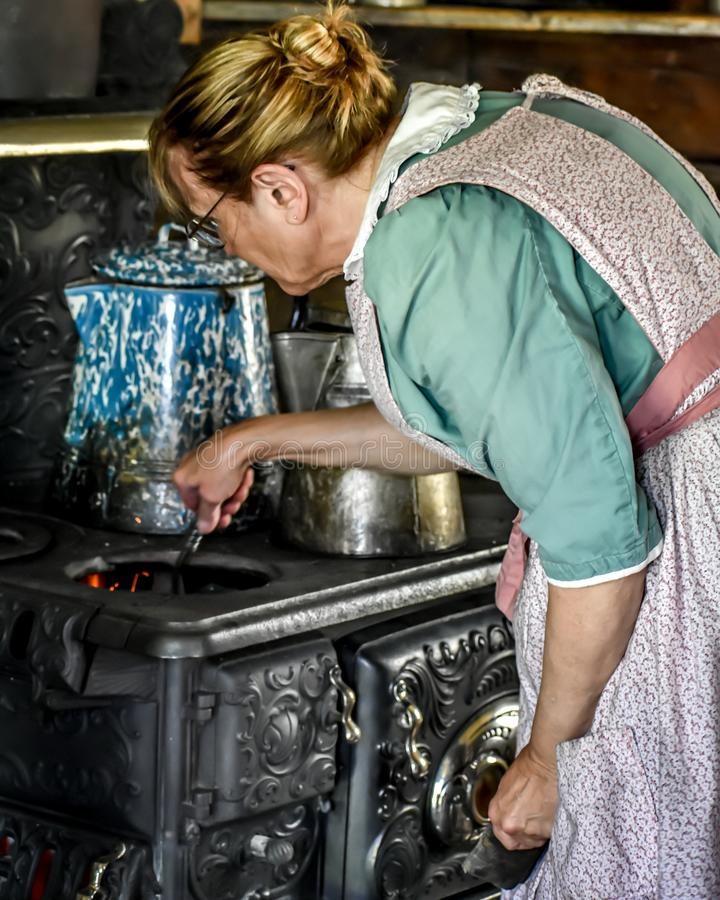 Pioneer Woman Stoking the Fire on a Cast Iron Woodstove stock photos