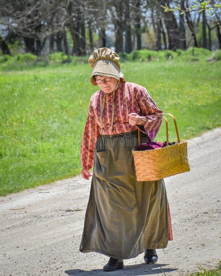 Pioneer Woman Walking Down Road stock photos