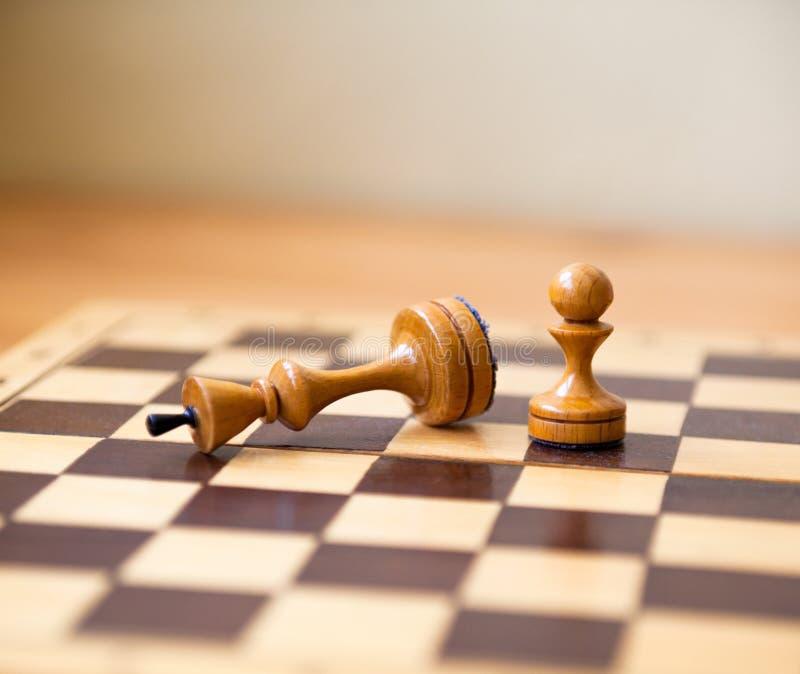 Pionek wygrywa zwycięstwo nad królewiątkiem kawa?ki szachowi zdjęcie stock