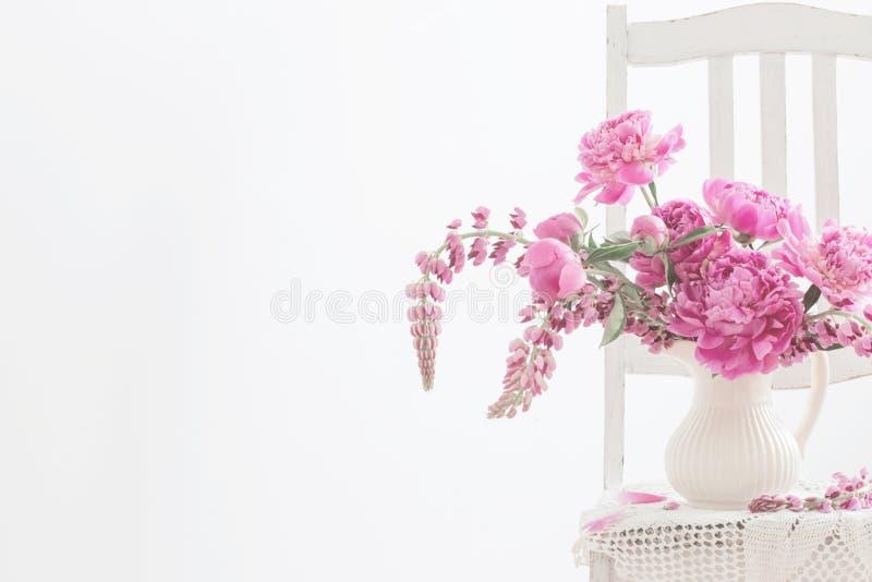 Pionen blommar i vas på tappningstol royaltyfri bild