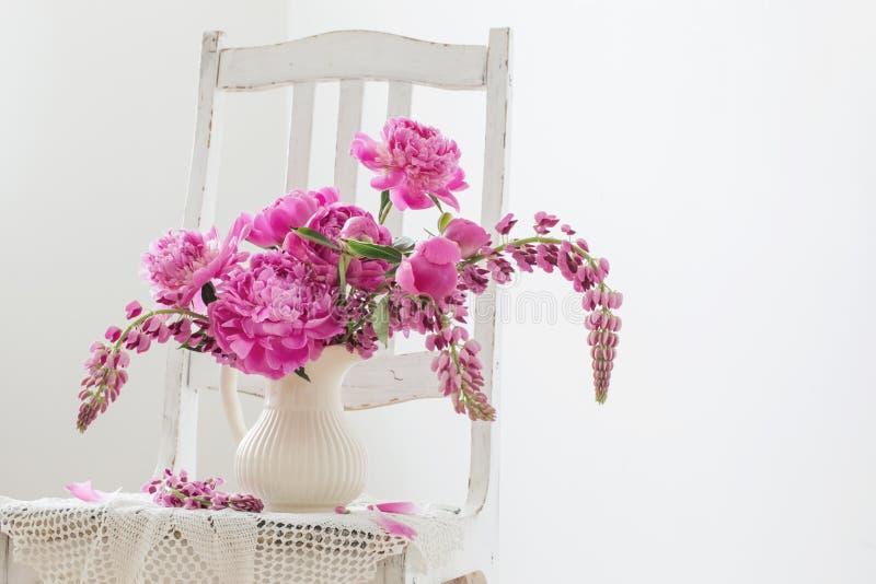 Pionen blommar i vas på tappningstol arkivbild