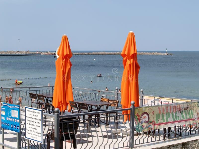 PIONIERE, RUSSIA Due ombrelli arancio della spiaggia contro lo sfondo del Mar Baltico immagini stock