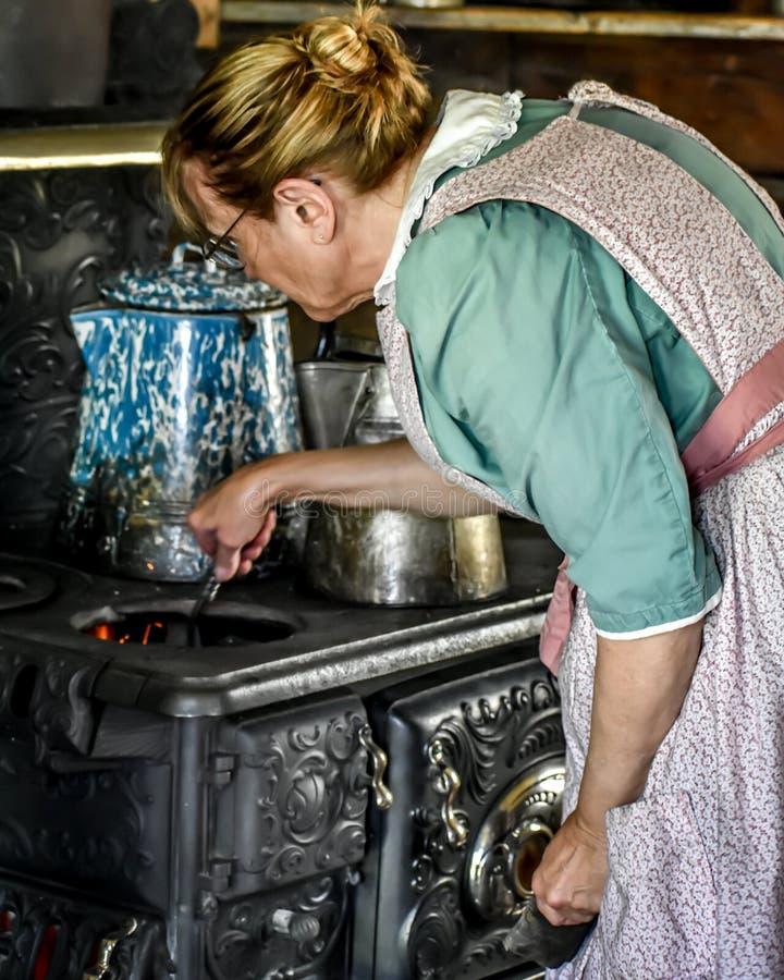 Pionierska kobieta Podsyca ogienia na Lanym Żelaznym Woodstove zdjęcia stock