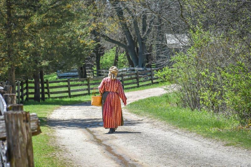 Pioniersvrouw die onderaan Weg lopen royalty-vrije stock afbeelding