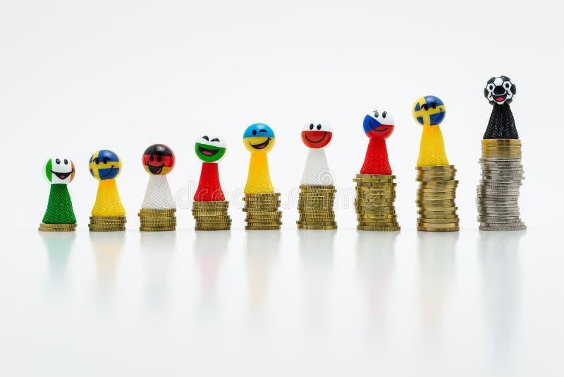 Pionkowie z uśmiechać się twarze w chorągwianych kolorach różnorodni kraje, stoi na dorośnięcie monetach Pojęcie rywalizacja i zw zdjęcia royalty free