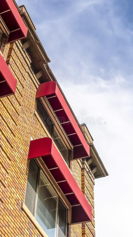 Pionowo budynku zewnętrzna uwypukla kamienna ściana z cegieł i czerwone markizy na okno obrazy stock