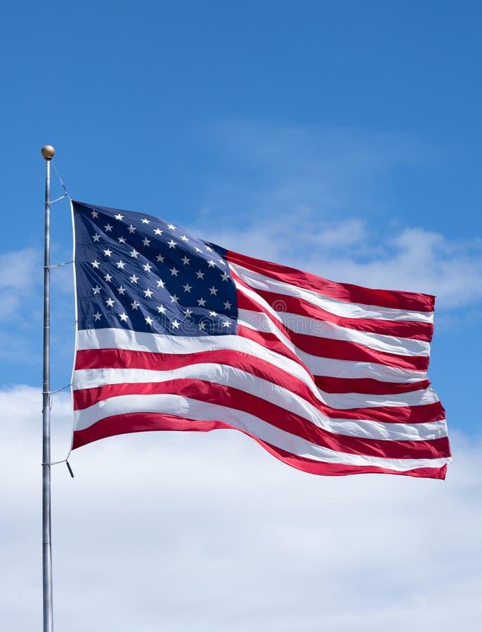 Pionowo flaga ameryka?ska na Chor?gwianym s?upie z niebieskim niebem i chmurami obrazy royalty free