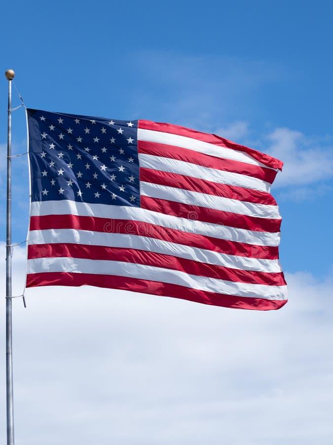 Pionowo flaga ameryka?ska na Chor?gwianym s?upie z niebieskim niebem i G?stymi Bia?ymi chmurami obraz stock