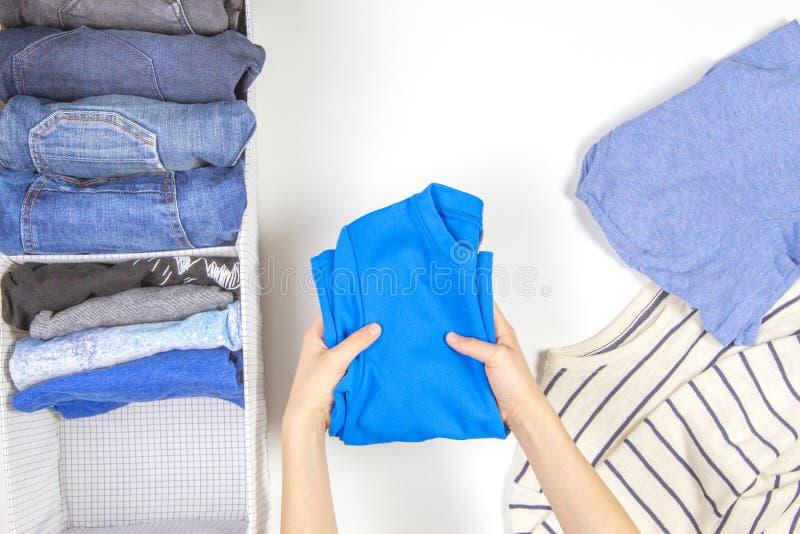 Pionowo magazyn odzież, sprząta w górę, izbowy czyści pojęcie Ręki sprząta w górę i sortuje dzieciaków odziewają w koszu obraz royalty free