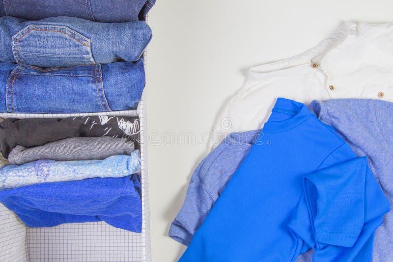 Pionowo magazyn odzież, sprząta w górę, izbowy czyści pojęcie Sterta fałdowa t koszula, cajgi w koszu z rozsypiskiem i zdjęcia stock