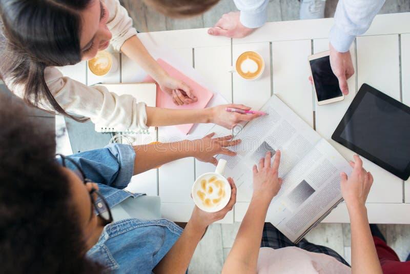 Pionowo obrazek cztery uczni studiować Wszystkie f one filiżankę kawy na stole Dziewczyny trzymają czasopismo i obrazy royalty free