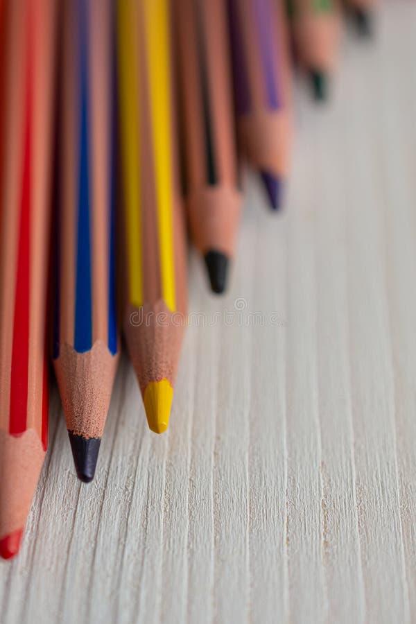Pionowo odgórny widok kilka barwioni ołówki na dobrze skupiającym się na lewicie z pionowo bokeh skutkiem, zdjęcie stock