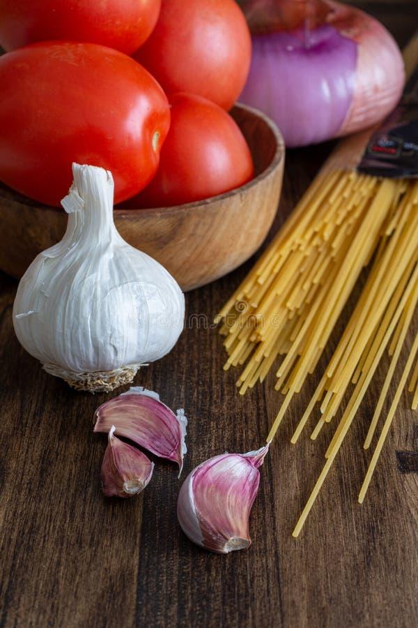 Pionowo odgórny widok składniki dla robić spaghetti, pomidorom, czosnku i cebul, fotografia royalty free