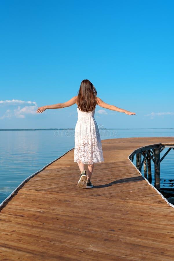 Pionowo portret brunetka w białej sukni od plecy iść z jej rękami otwartymi na drewnianym molu pojęcie wolność, zdjęcie stock