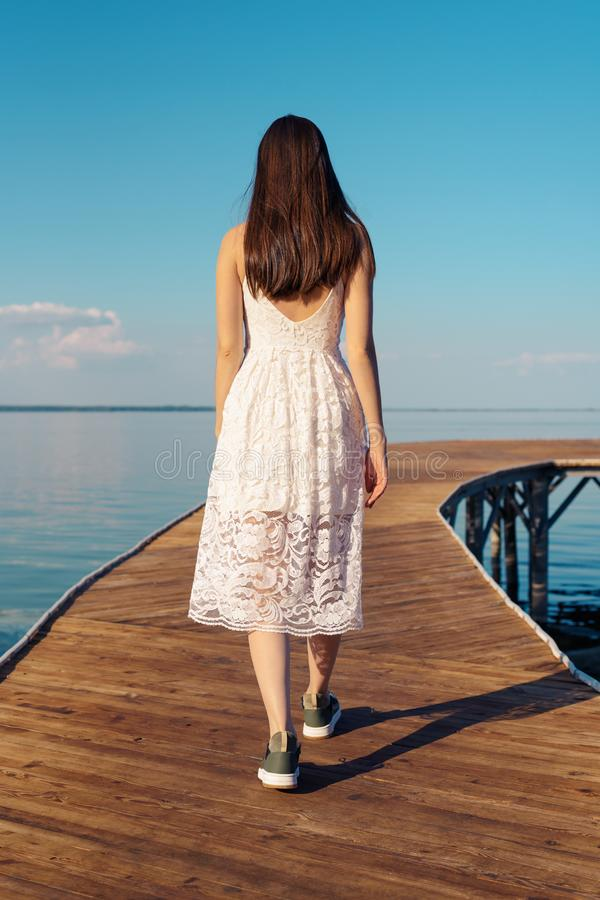 Pionowo portret brunetka w biali sundress od plecy jest na drewnianym molu obraz stock