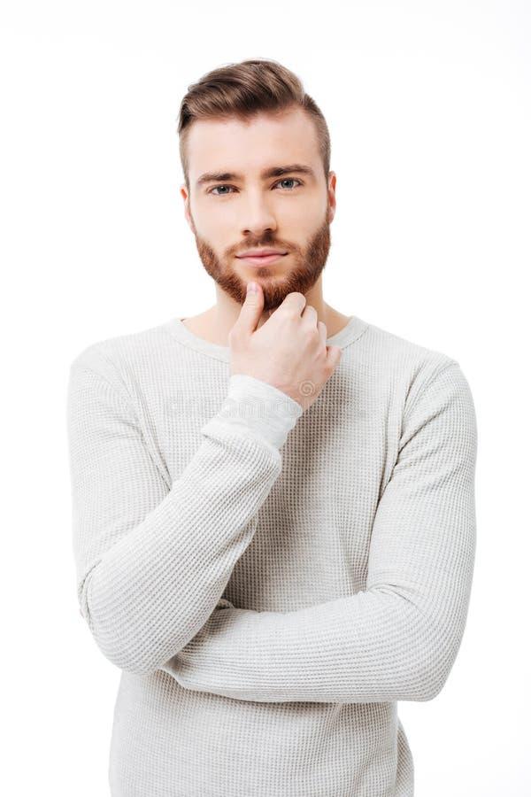 Pionowo portret młody przystojny mężczyzna patrzeje kamerę nad białym tłem Atrakcyjny brodaty facet trzyma jego zdjęcie royalty free