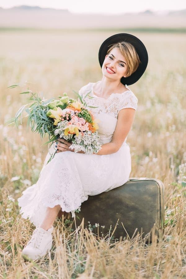 Pionowo portret rocznik ubierał panny młodej trzyma ślubnego bukiet colourful kwiaty, siedzi na fotografia stock