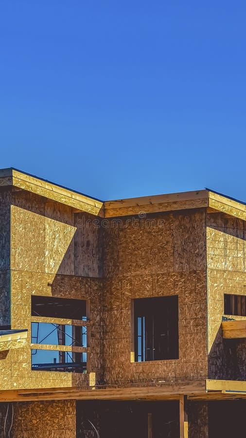 Pionowo powierzchowność dom w budowie przeciw jasnemu niebieskiemu niebu na słonecznym dniu obraz royalty free