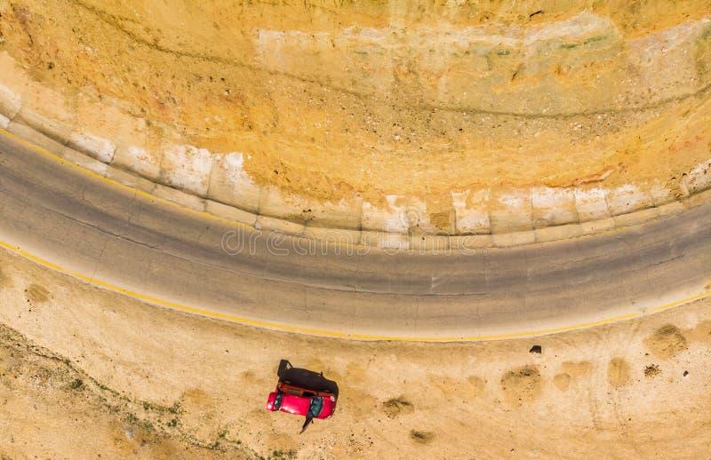 Pionowo powietrzna fotografia falezy i droga przy Nieżywym morzem w Jordania, z parkującym czerwonym samochodem brać z trutniem fotografia royalty free