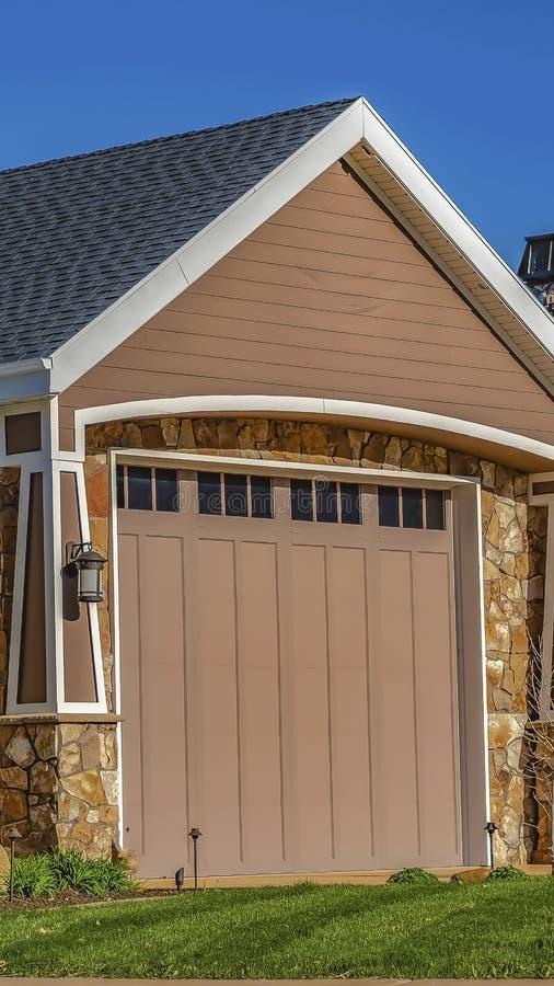Pionowo rama dom z garażu drzwiowym trawnik przed domem i metal bramą przeglądać przeciw jasnemu niebieskiemu niebu obraz royalty free