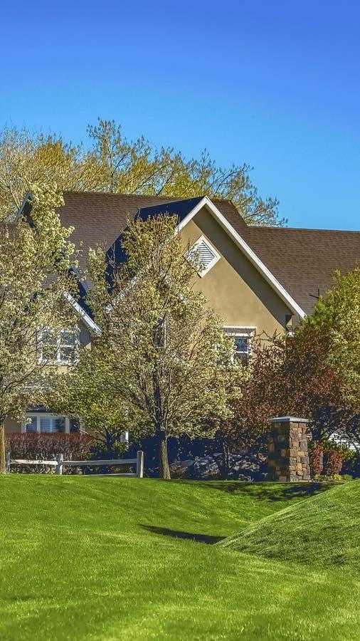 Pionowo ramowa fasada dom na szerokim trawiastym terenie pod jasnym niebieskim niebem na słonecznym dniu obraz royalty free