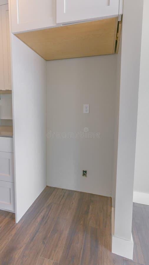 Pionowo ramowy wnętrze kuchnia z wiszącym gabinetem nad pusty chłodziarka alkierz obraz stock